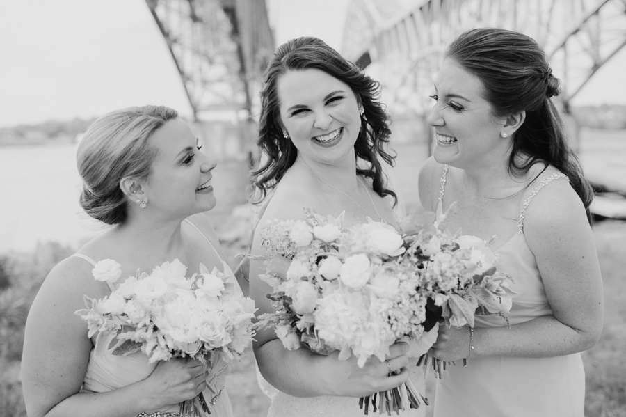 black and white of bride with bridesmaids smiling at each other