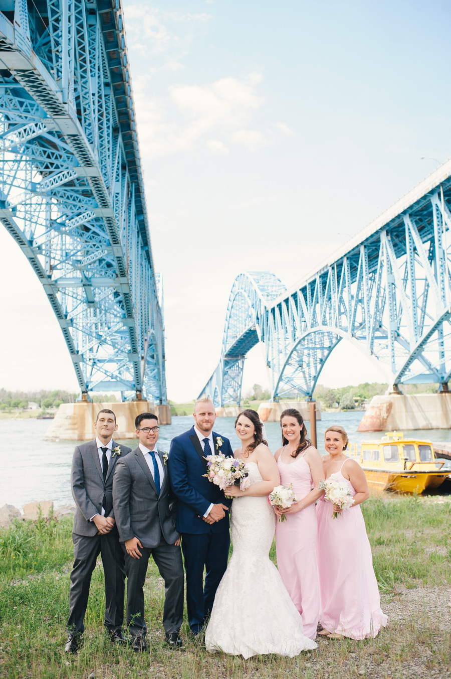 wedding party lined up under the grand island bridge