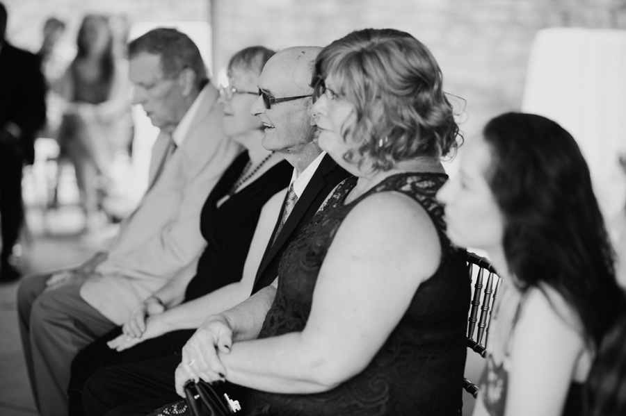black and white of bride and groom's parents looking on during the ceremony