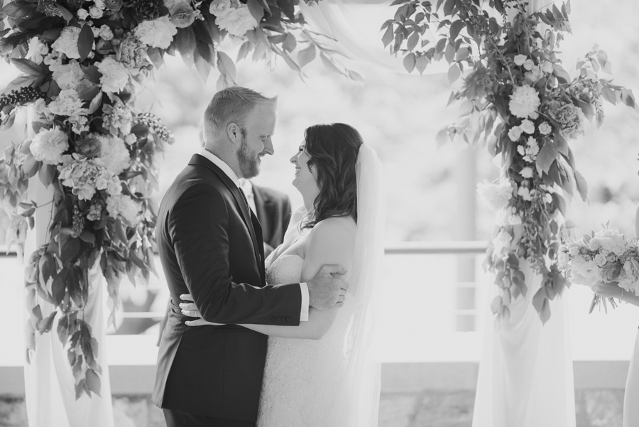 black and white of bride and groom holding each other and smiling under the floral arbor