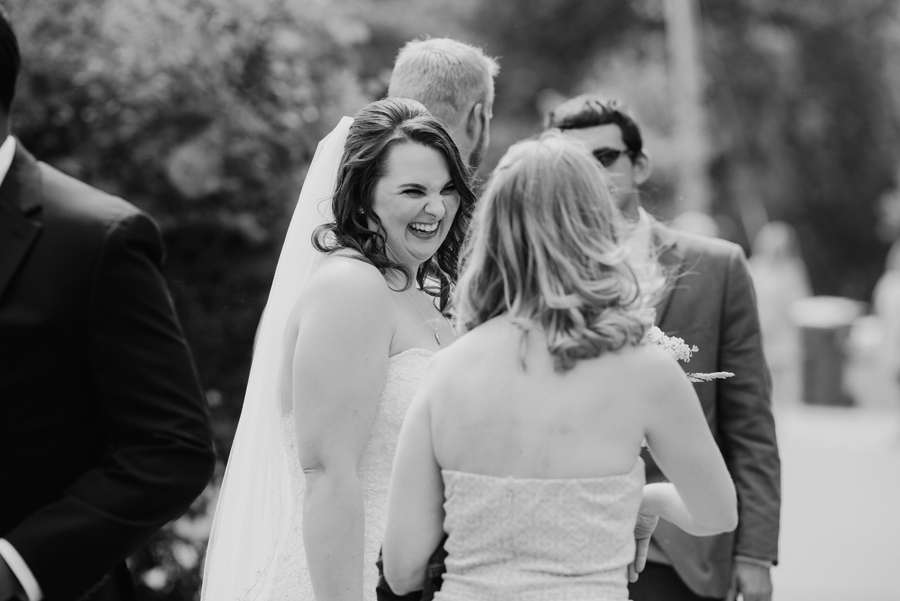 black and white of bride laughing with wedding guests