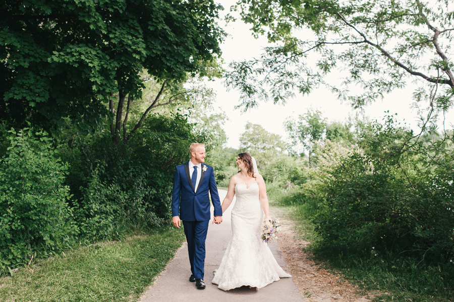 bride and groom strolling hand in hand through delaware park