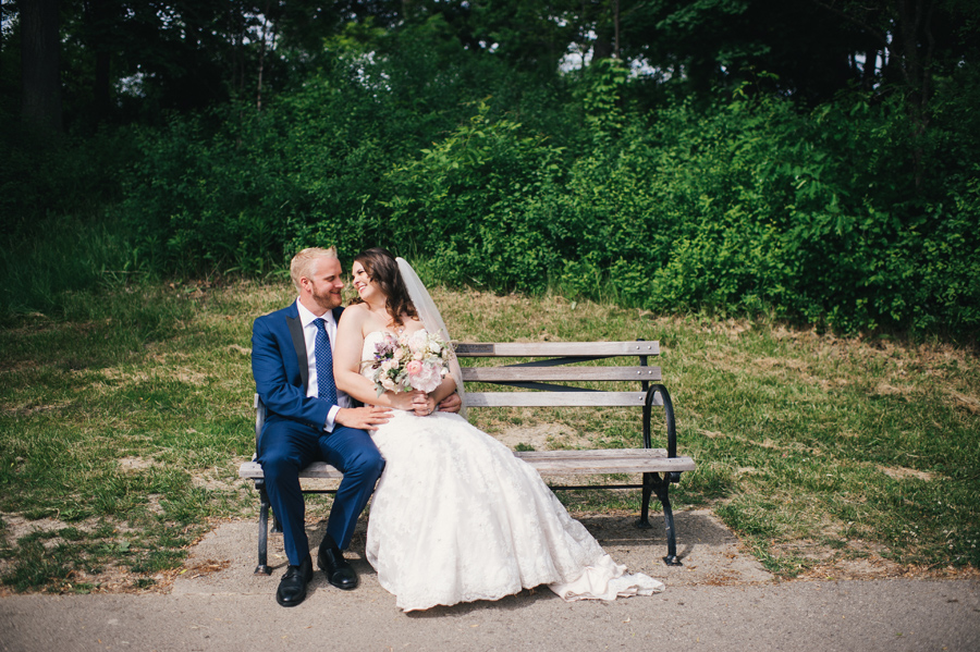 bride and groom sitting on a bench together at delaware park