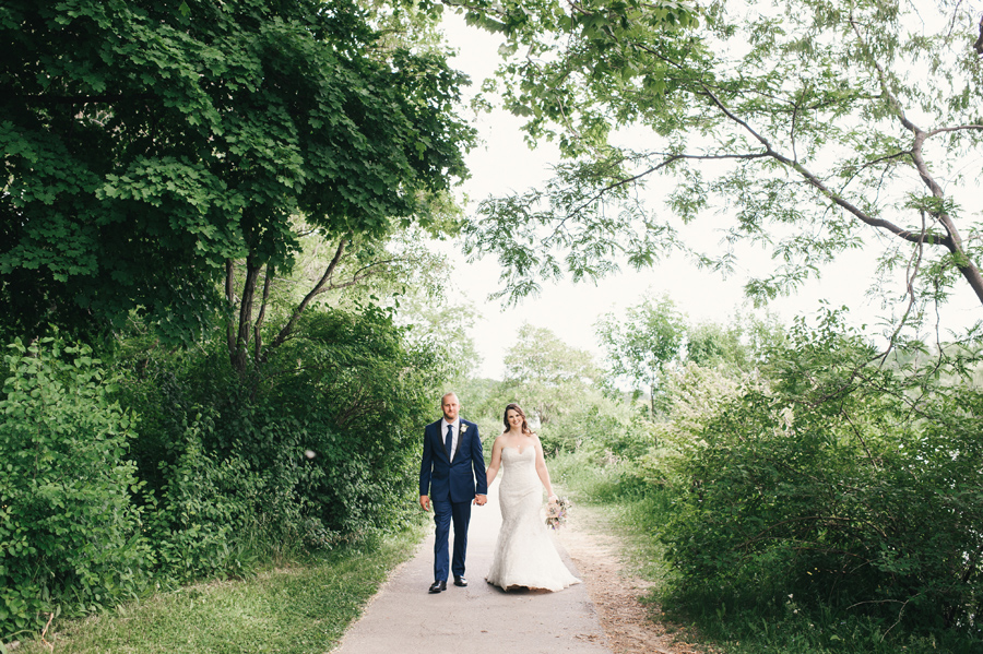 bride and groom walking the path together through delaware park