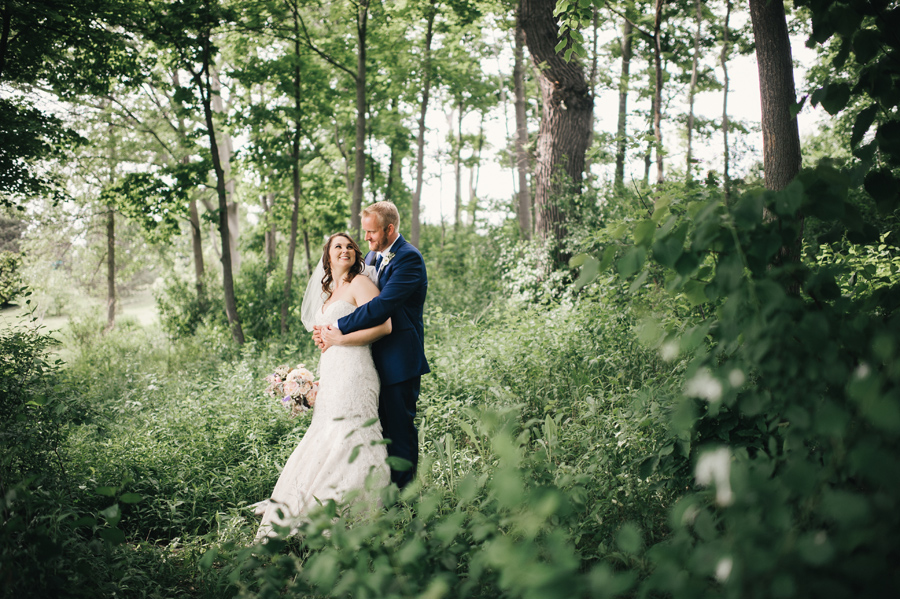 bride and groom standing together in a wooded area