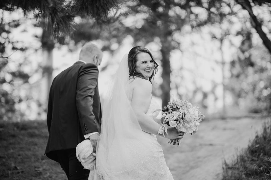 black and white of bride and groom walking up a path together