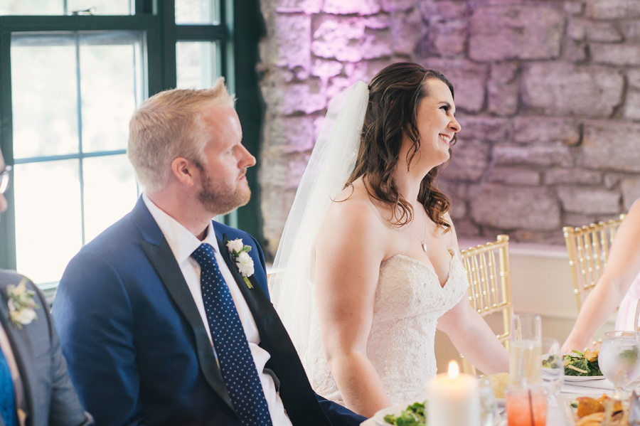 bride and groom smiling together during speeches