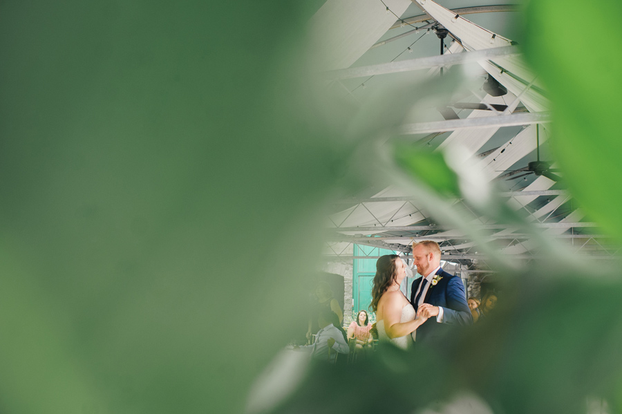 shot of bride and groom dancing through leaves