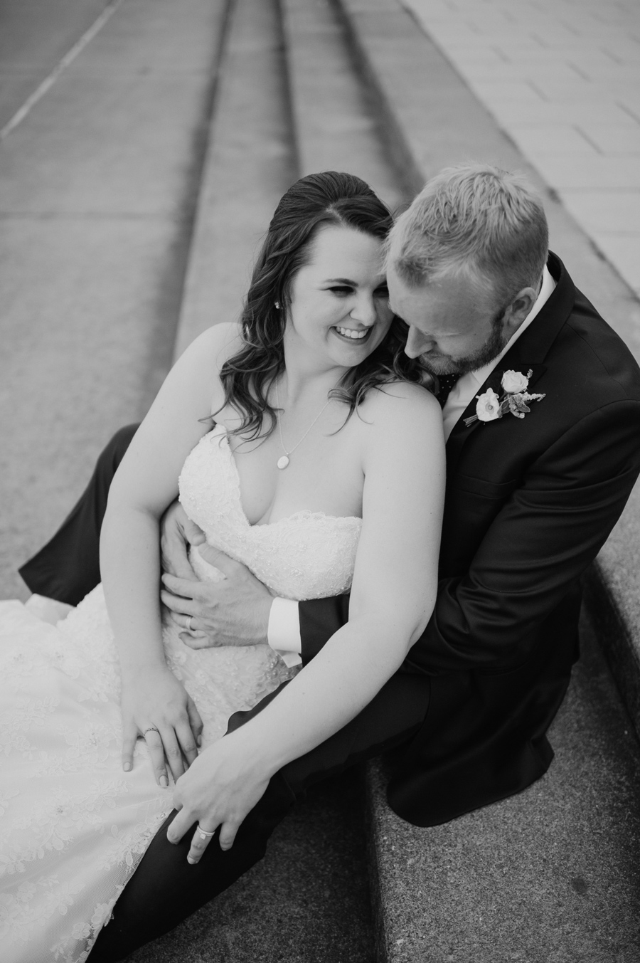 black and white portrait of bride and groom on steps outside