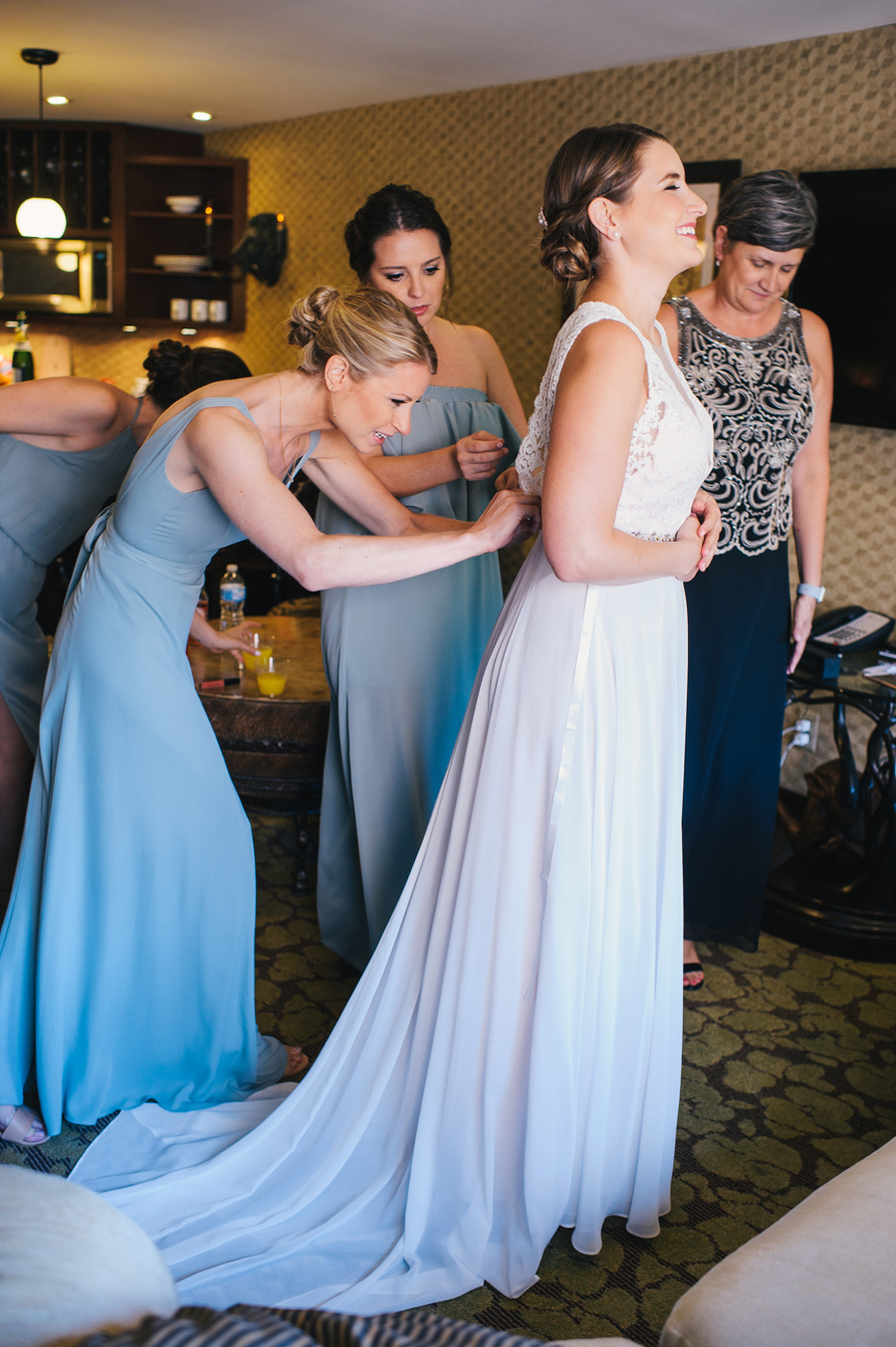 bridesmaids buttoning the back of the bride's dress