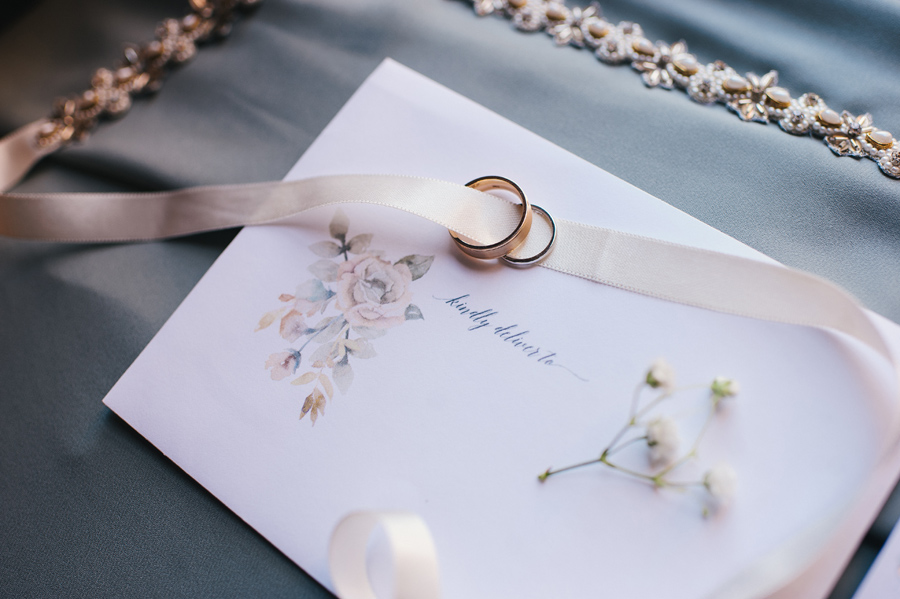 close up of wedding rings with bridal belt and RSVP card