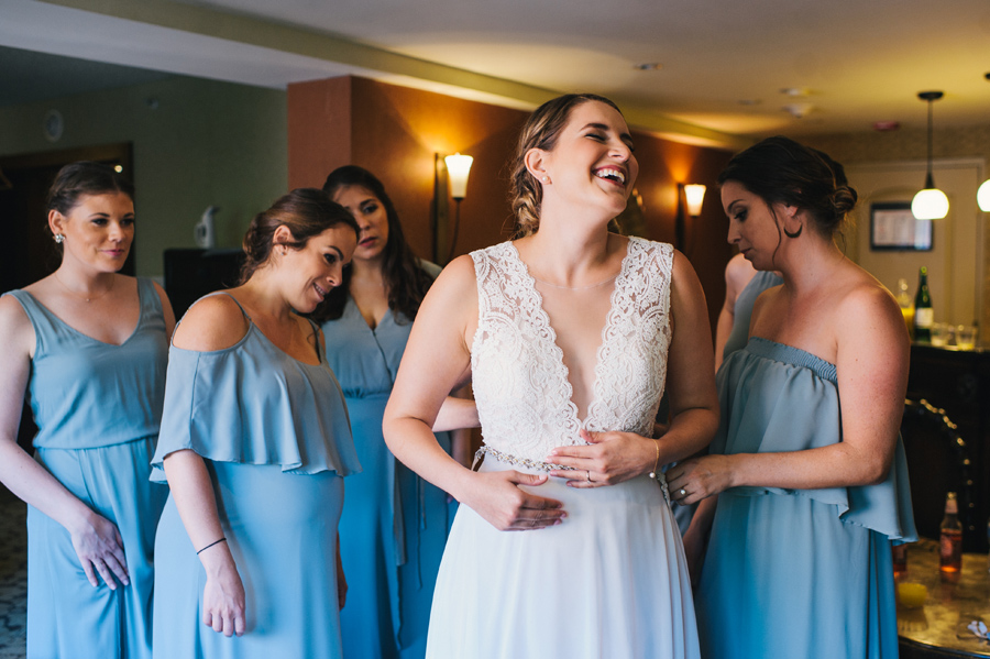 bride laughing while bridal party buttons the back of her dress