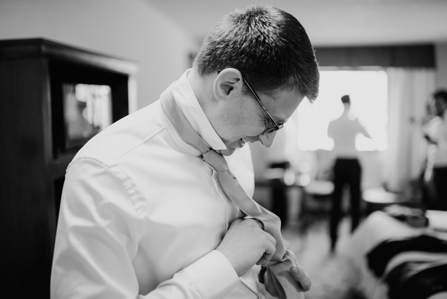 black and white of groom adjusting his tie on wedding morning
