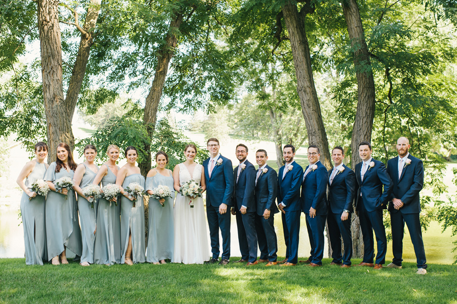 full length shot of the entire 15 person wedding party wearing shades of robins egg and navy blue