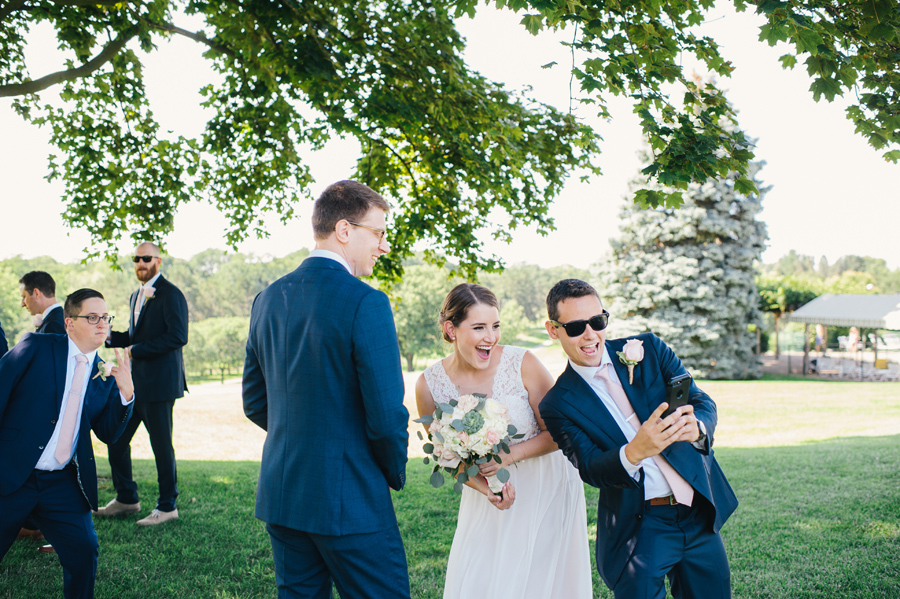 bride taking a selfie with a groomsman