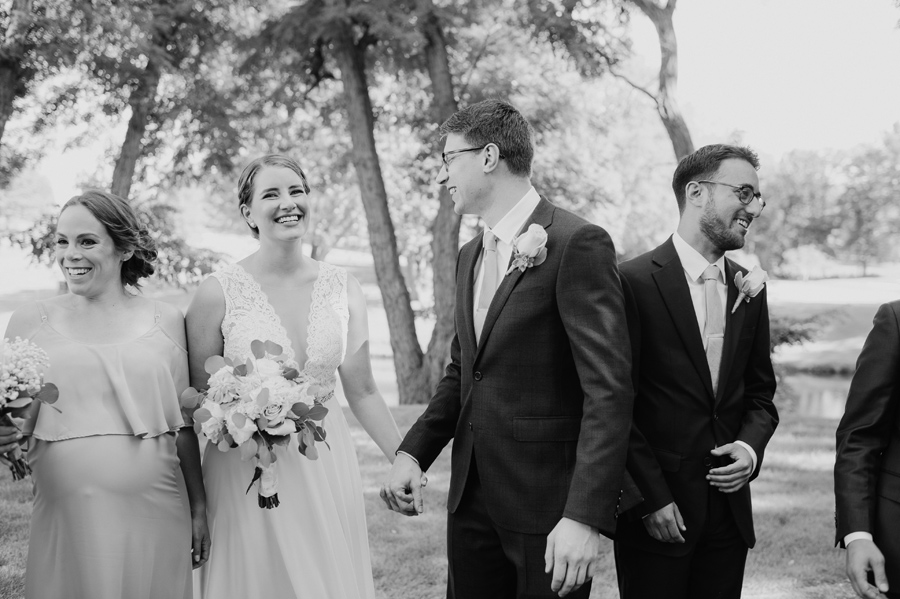 black and white of bride and groom holding hands and smiling while casually hanging out with wedding party
