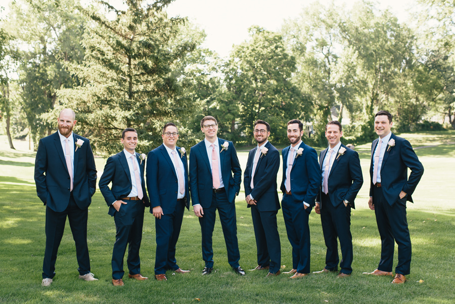 full length of groomsmen in navy suits with light pink ties standing in a park