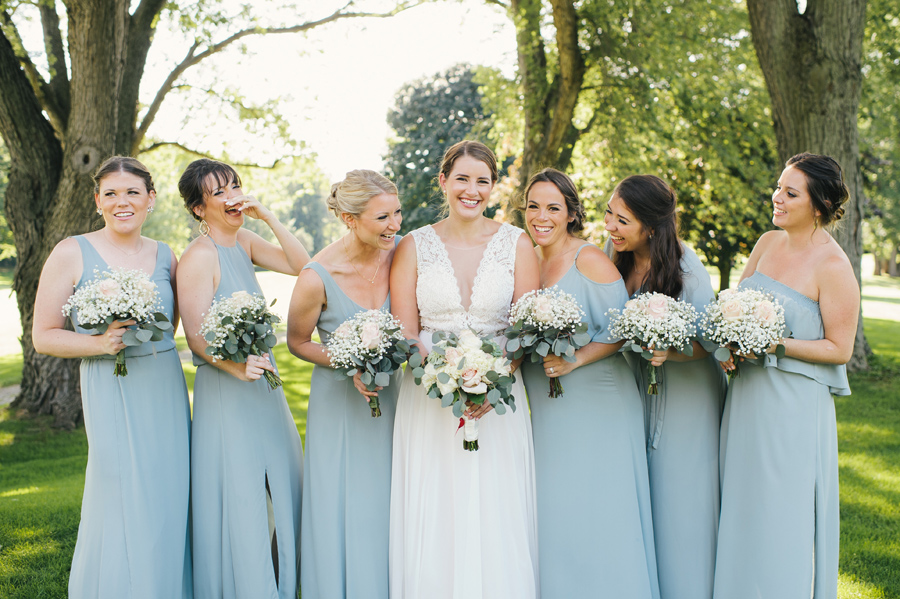 bride and bridesmaids laughing together in a park while posing for the camera
