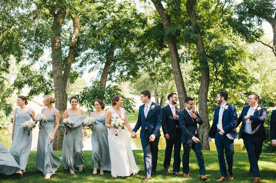 full length of entire wedding party laughing together and walking towards camera in the park