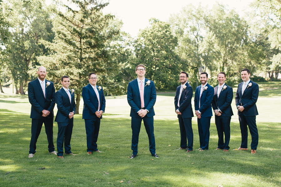 groom and groomsmen posing for the camera on a golf course