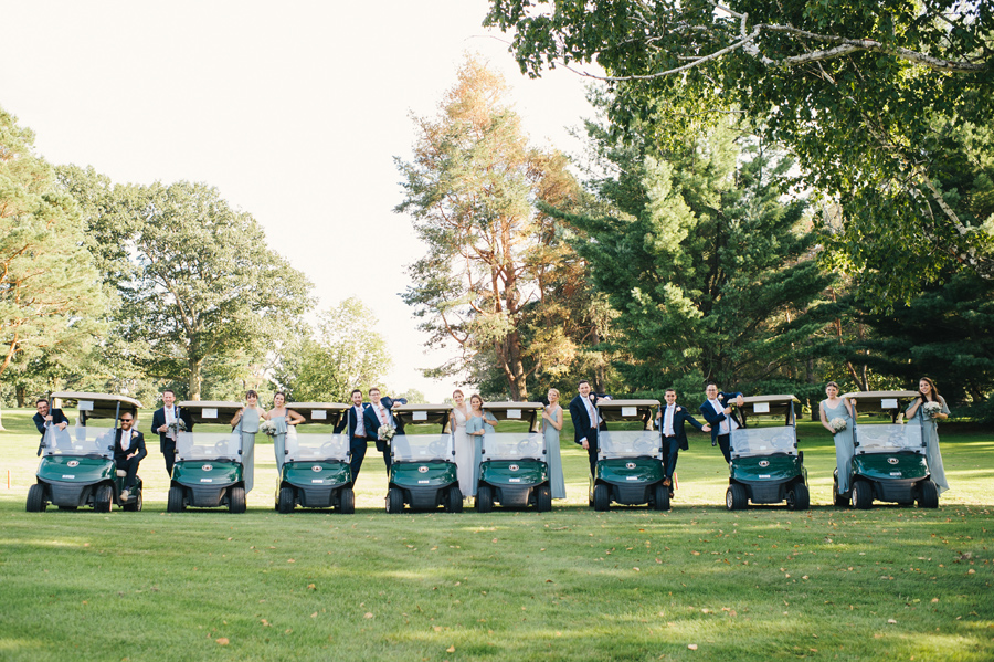 8 golf carts lined up with wedding party members leaning out of the sides