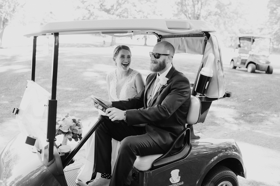black and white of bride laughing while her brother drives her in a golf cart