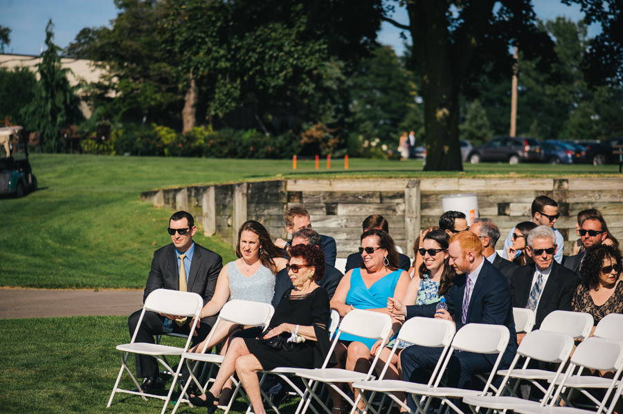 wedding guests sitting in ceremony chairs before the wedding begins