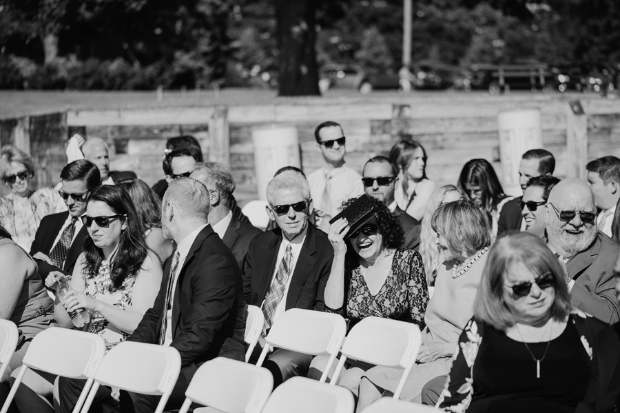 black and white of wedding guests shielding their eyes from the sun