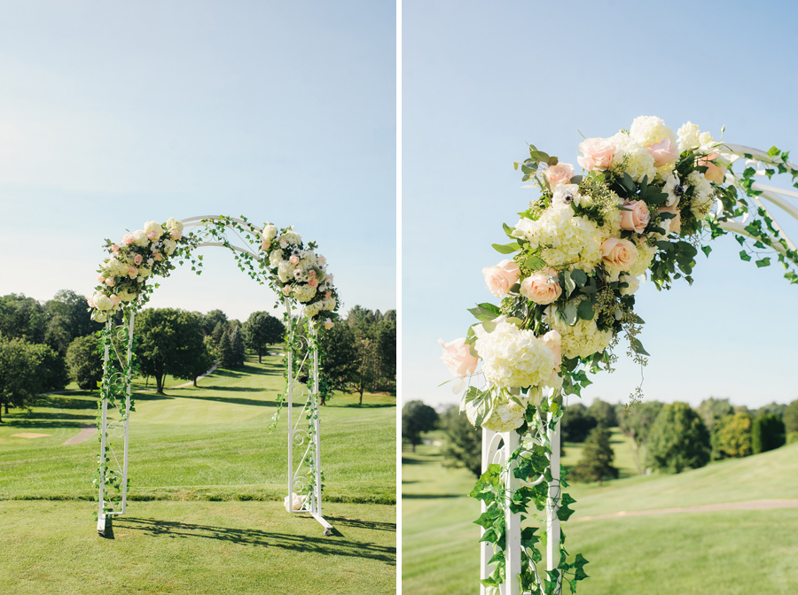 floral ceremony arch of white metal and white and blush pink flowers with greenery and vines