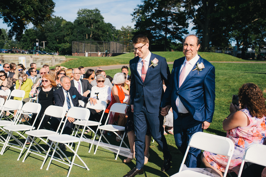 groom's parents walking him down the aisle at the outdoor golf course ceremony