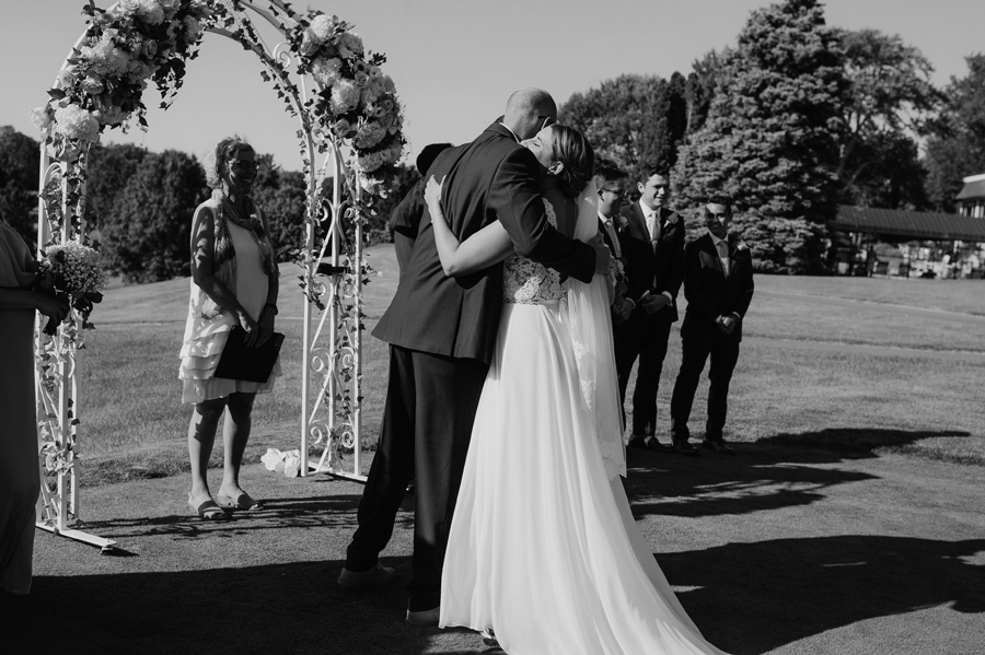 black and white of bride hugging her brother at the altar