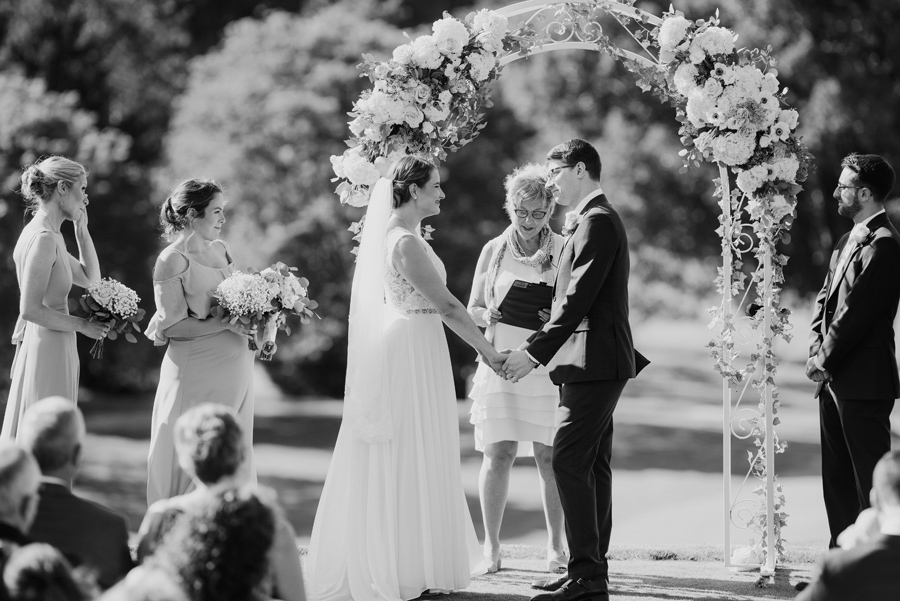 black and white of bride and groom holding hands under their floral arch during the wedding ceremony