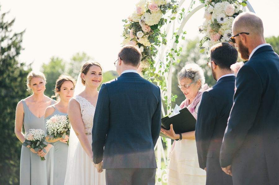 bride smiling at groom under a floral arch during their outdoor wedding ceremony