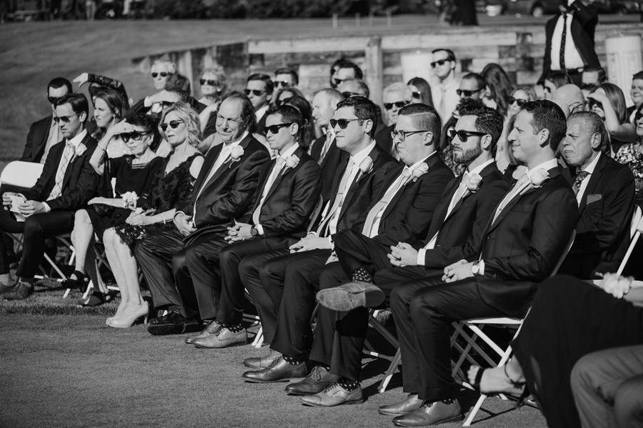 black and white shot of groomsmen and other seated guests watching the wedding ceremony on a golf course