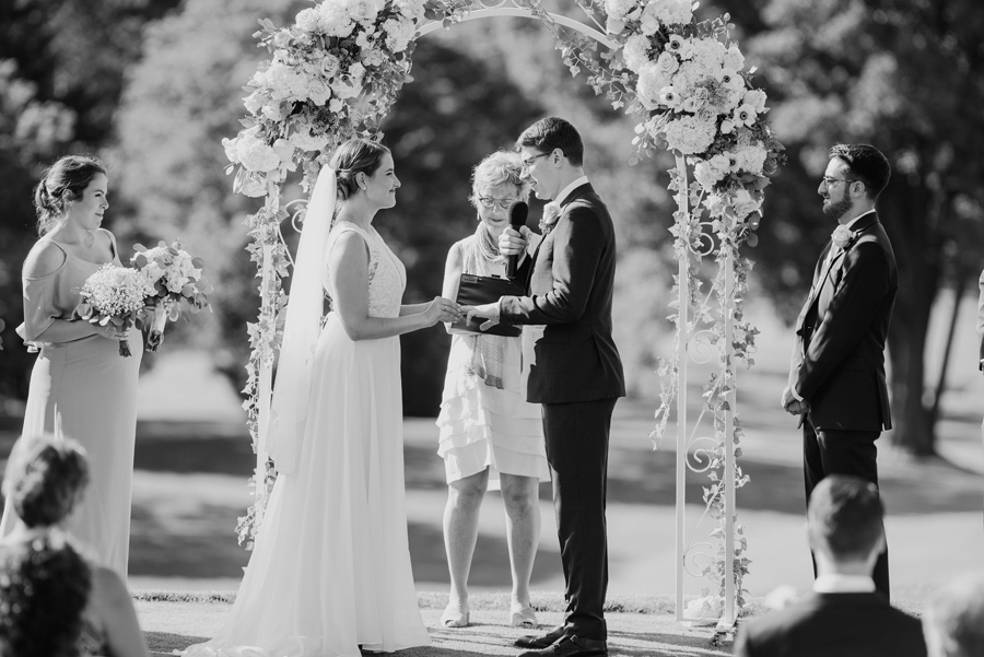 black and white shot of bride placing wedding band on groom's finger during their outdoor ceremony