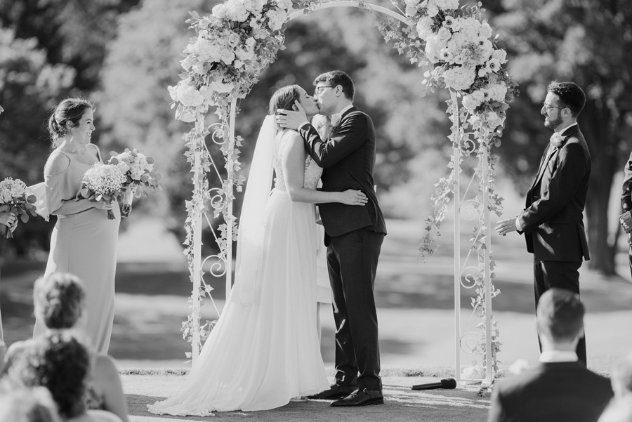 black and white shot of bride and groom's i do kiss at golf course wedding ceremony