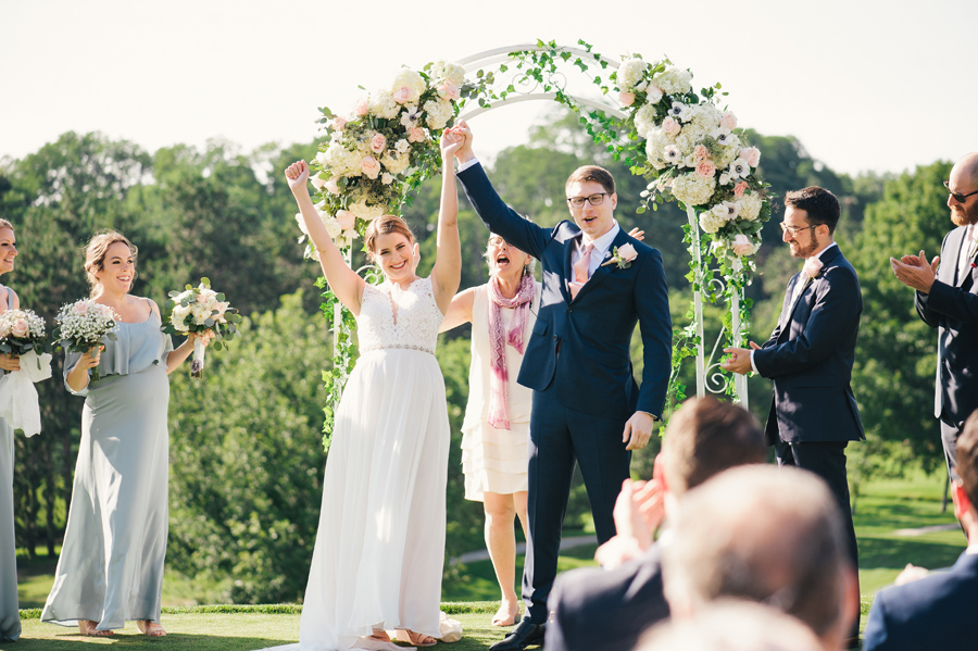 bride and groom facing their guests with arms raised as they're announced as officially married