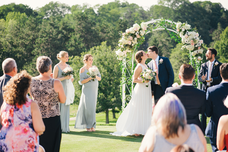 bride and groom kiss under their floral archway at the end of their outdoor country club wedding ceremony