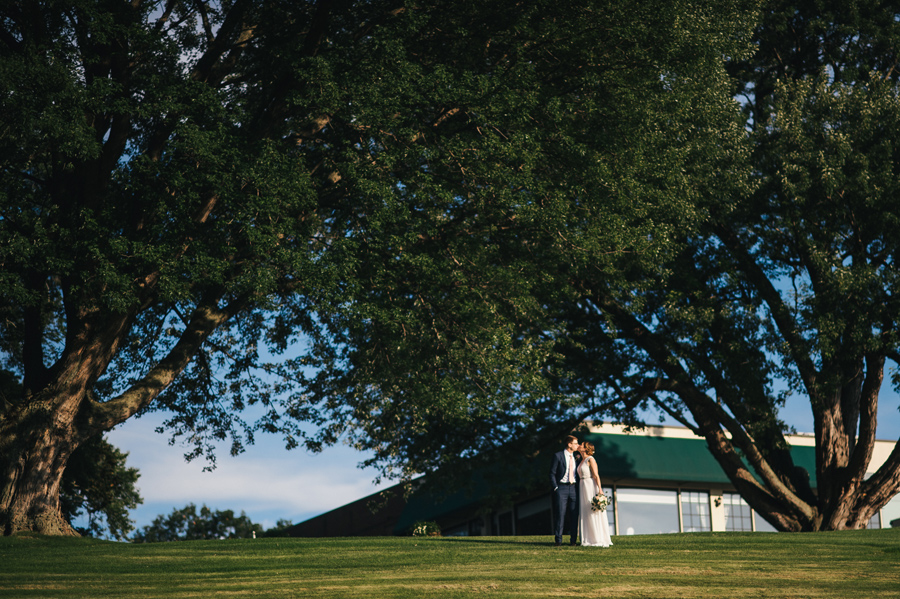 distant shot of bride and groom kissing on the ground of their country club wedding