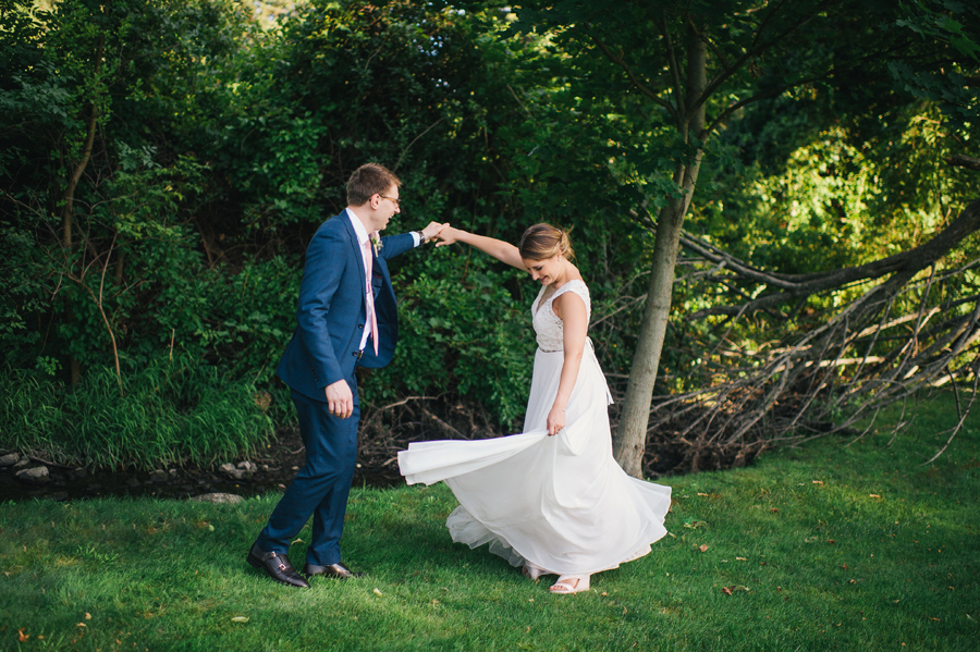 groom twirling his bride near a stream in a wooded area
