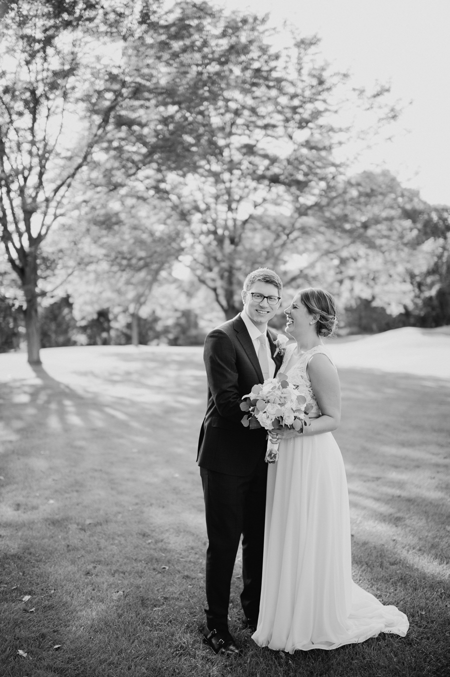 black and white portrait of groom smiling at the camera while bride laughs