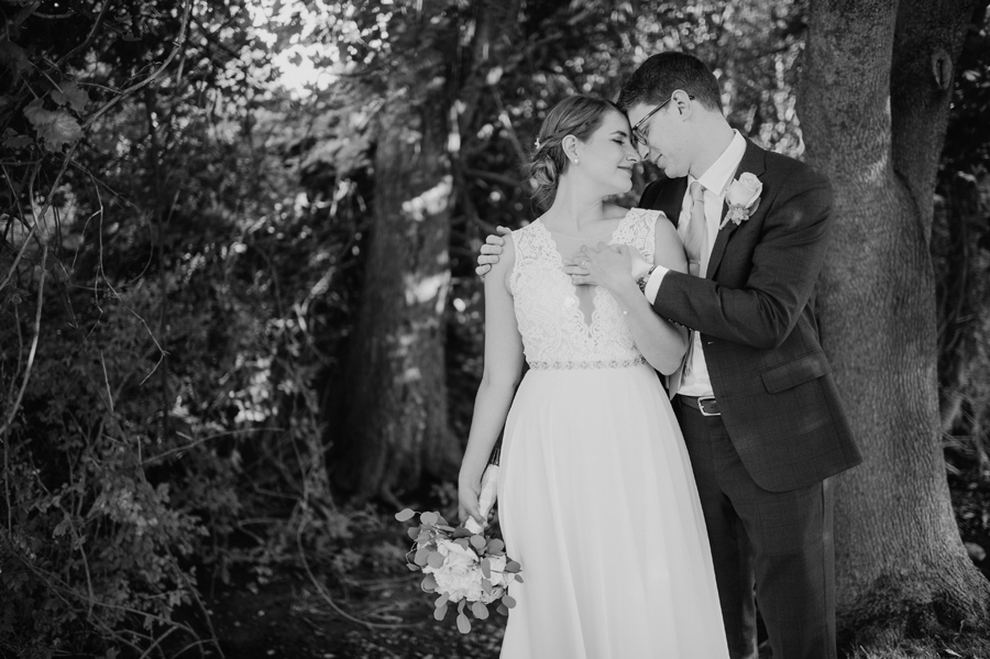 black and white of bride and groom touching foreheads with their eyes closed and embracing