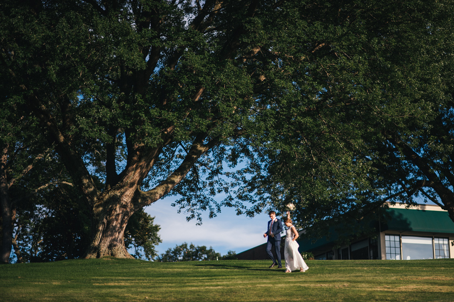 bride and groom running through the country club grounds together