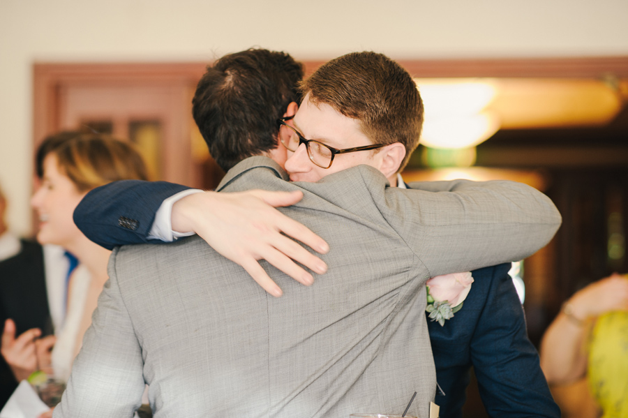 groom hugging a wedding guests as he enters the reception