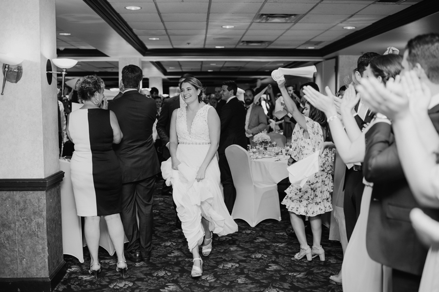 bride and groom running into wedding reception while guests cheer and waive dinner napkins in the air
