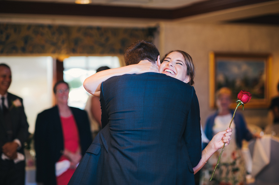 groom hugging a smiling bride after giving her a single red rose during their first dance
