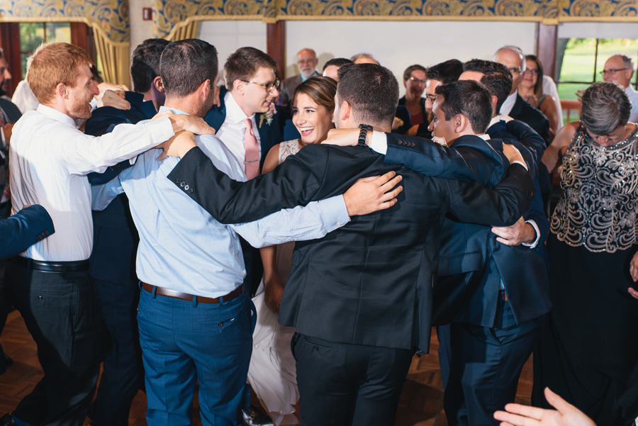 wedding guests circling around bride and groom on the dance floor