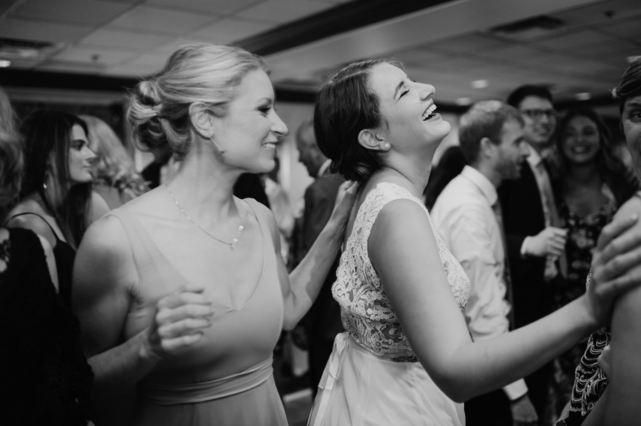 bride and bridesmaid laughing and dancing during the hora