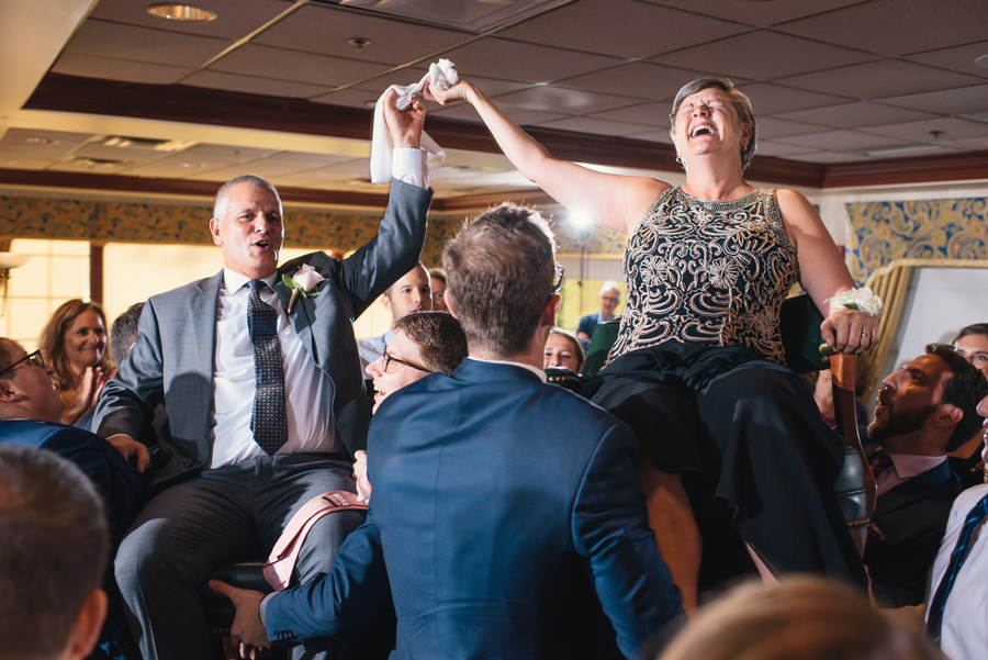 parents of the bride being raised in chairs during the hora and laughing