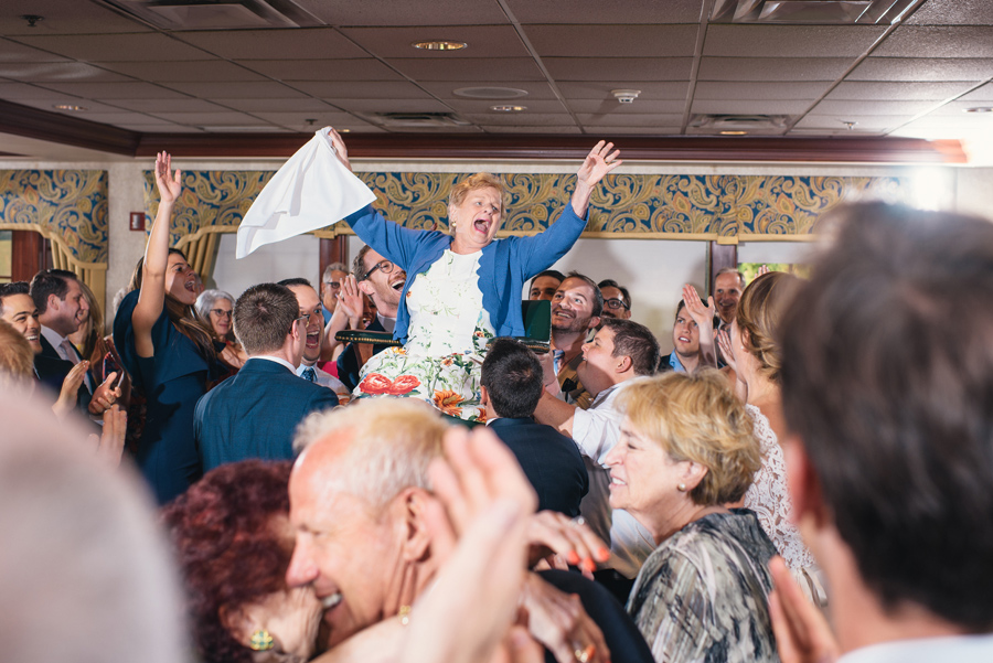 grandmother throwing her arms up while being raised in chair during the hora